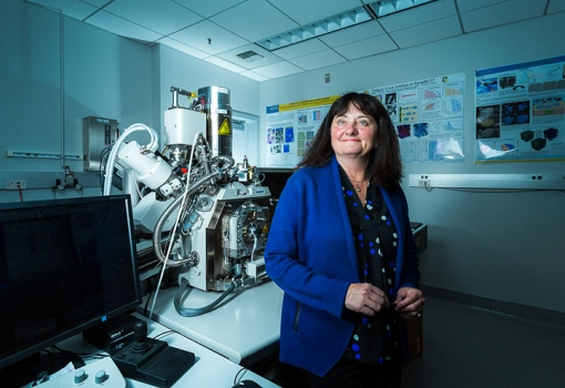 Tresa Pollock beside a combined laser and electron-beam tomography system