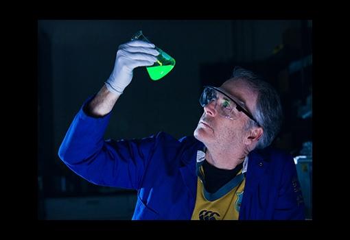 Professor Craig Hawker examines a vial of fluorescing green liquid.
