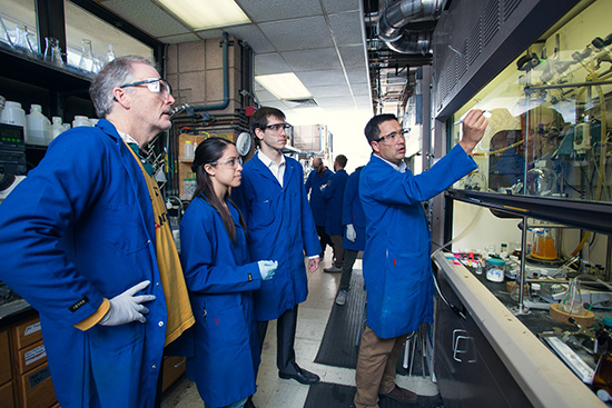 Faculty and students discuss a formula in the Dow lab.